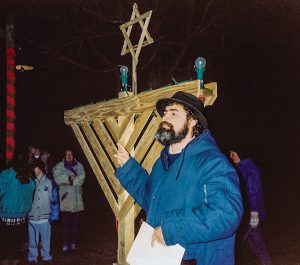 Moshe Gresser and a large wooden menorah.