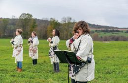 Jessica Posner and student artists in bathrobes in a field