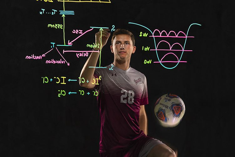 Oliver Harris '19 in soccer uniform before transparent chalkboard