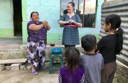Two women lead children in hand-washing demonstration