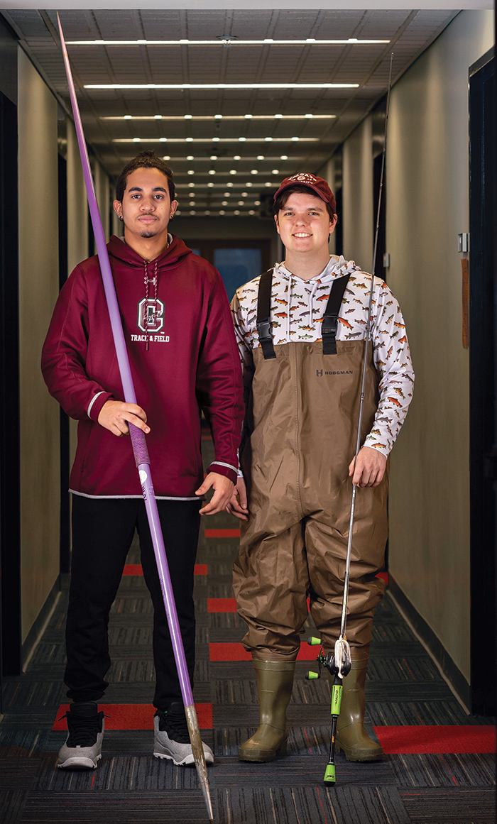 Cruz, holding a javelin, and Hoit, holding a fishing pole, standing next to each other in their dorm room hallway.
