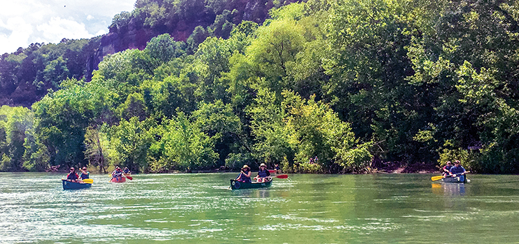 Students canoeing on river