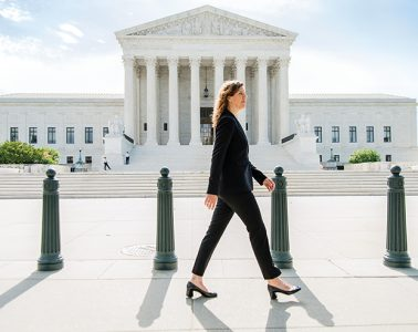 Katie Redford '09 walking in front of supreme court building