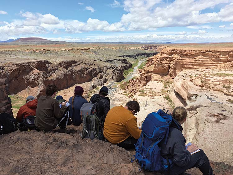 Students taking notes on edge of canyon