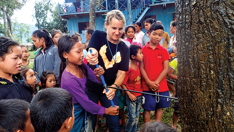 Coffman teaches Laotian children how to use a tree borer to sample Asian swamp cypress.