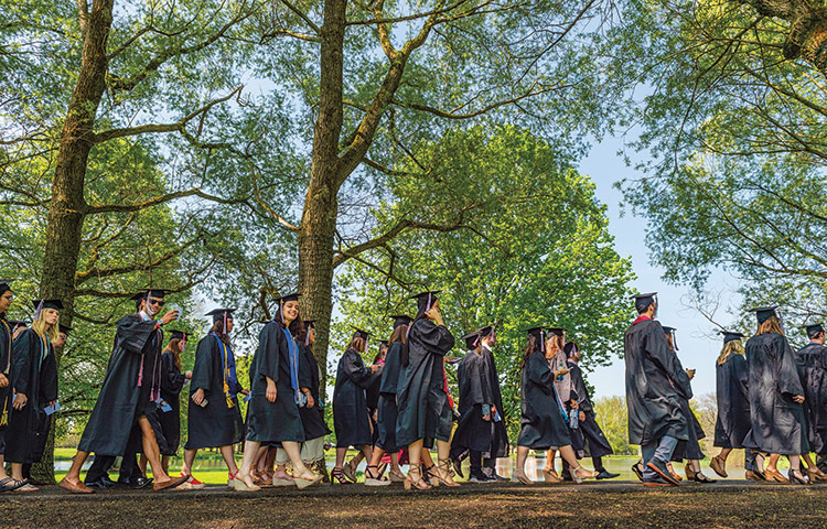 Students in caps and gowns during outdoor commencement procession