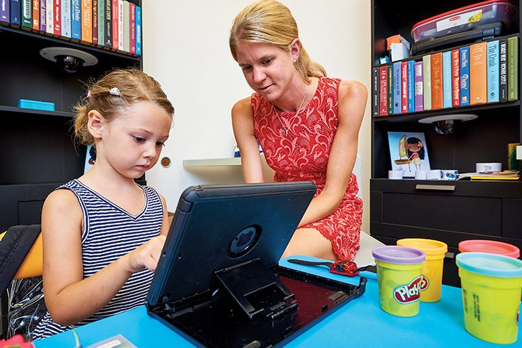 Professor working with child on ipad
