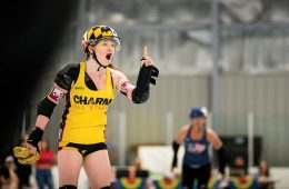 woman in roller derby gear pointing a finger confrontationally