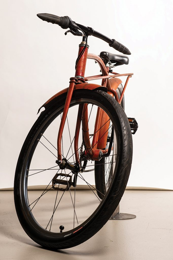 Front view of a rusty orange bike with flame details