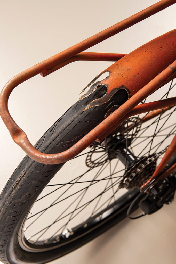 Close up of a rusty orange bike with flame details