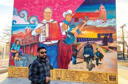 Muralist standing infront of mural of folk musicians