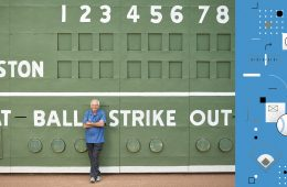 Joe Castiglione '67 leaning against green baseball scoreboard