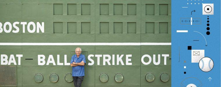 Joe Castiglione '67 leaning against green baseball scoreboard