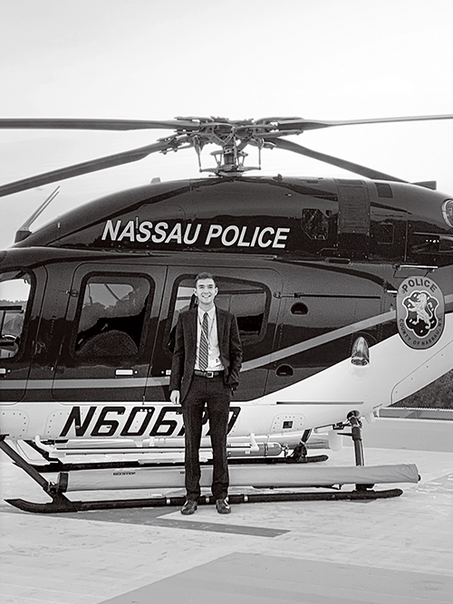David Little standing by a Nassau Police helicopter