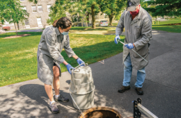 Geoffrey Holm, Associate Professor of Biology along with Michelle Landstrom, Surveillance and Monitoring Technician, use a GLS Sampler to collect samples of waste water