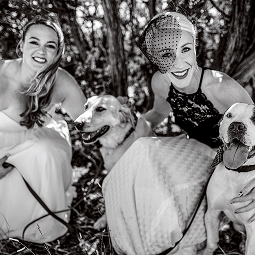 Emmi and Jesse in wedding attire with two of their dogs