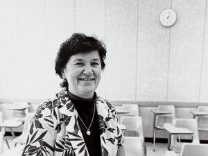 Gertrude Decker Pownall wearing a floral shirt, seated on a classroom desk