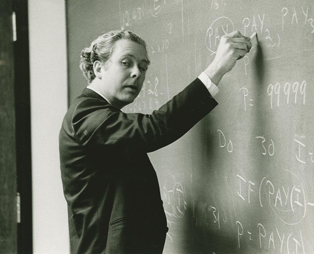 Brackett writes on the chalkboard.