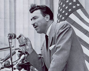 Adam Clayton Powell speaking at a podium