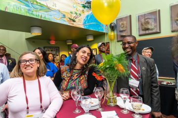 Audience members smiling and listening at the ALANA Cultural Center celebration