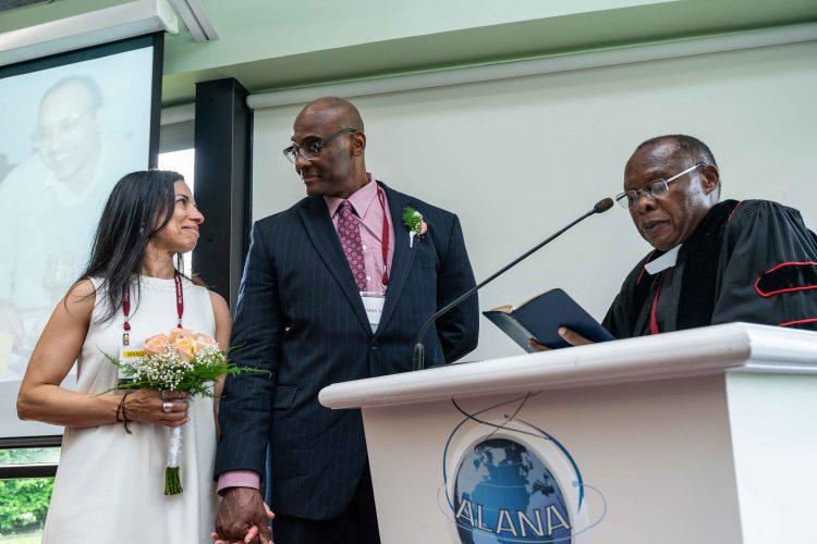 Teresa Delgado '88 and Pascal Kabemba '85 gaze at each other, standing before Harvey Sindima at podium