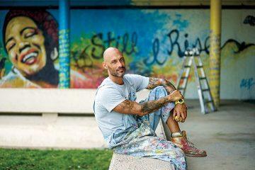 "Portrait of German DuBois in front of ""Still I Rise"" mural"