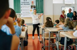 Oneida Shushe '19 stands in front of an elementary school class in Pristina, Kosovo