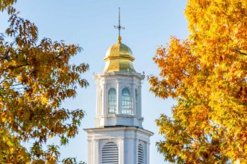 Chapel spire flanked by fall foliage