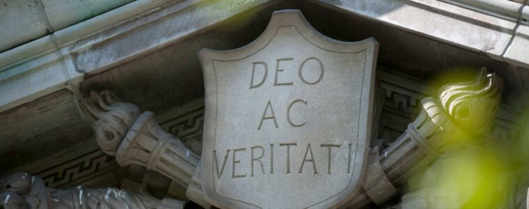 """Detail on campus building: """"Deo ac Veritati"""" on a shield"""