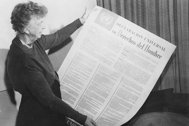 Eleanor Roosevelt holds up a copy of the Universal Declaration of Human Rights in Spanish.