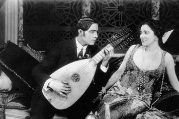 Rudolph Valentino plays a guitar for Nita Naldi on the set of the silent film Blood and Sand, 1922