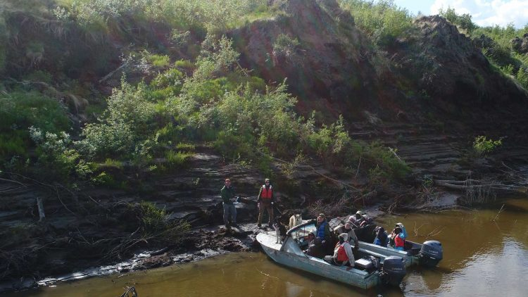 Team accesses field sites in small boats that float along the riverbank