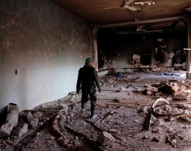 A member of a Christian armed militia Sutoro walks among ruins of a Sufi shrine belonging to Sheikh Khaznawi blown apart by ISIS in Tel Marouf or Tal (Credit: Eddie Gerald / Alamy Stock Photo)