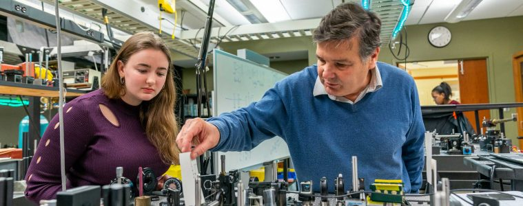 """Enrique """"Kiko"""" Galvez, Charles A. Dana Professor of Physics and Astronomy works with students in the laser lab in the Ho Science Center."""
