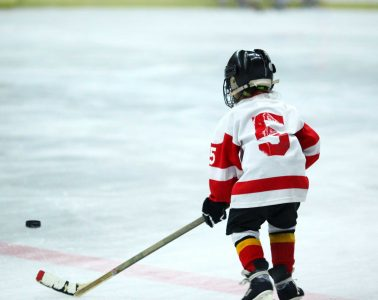 child wearing hockey gear skates in rink