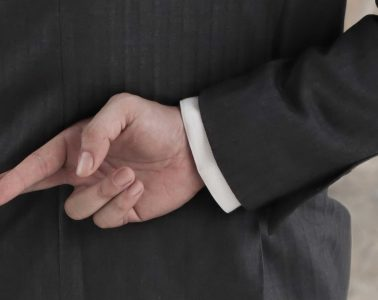 Man in business suit crosses fingers behind back