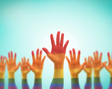 Raised hands painted in rainbow colors