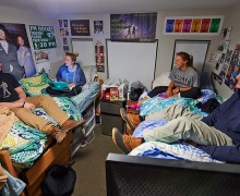 Students sitting on beds, talking, in Curtis Hall