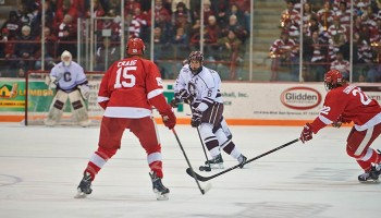 Colgate player has possession of the puck against Cornell
