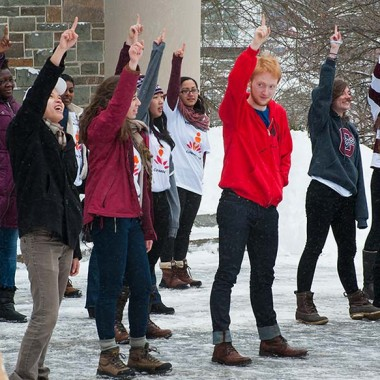 Students in a flash mob on the Quad all show the number 1 with their fingers