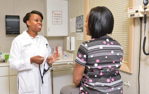 Yvonne Okoh Onyike '99 tends to a patient in a doctor's office