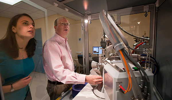 Professor Roger Rowlett and a student work with an X-ray  diffractometer.