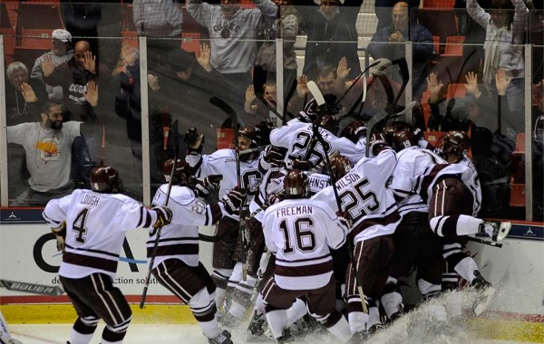 Hockey team celebrates game-winning goal in corner of the ice