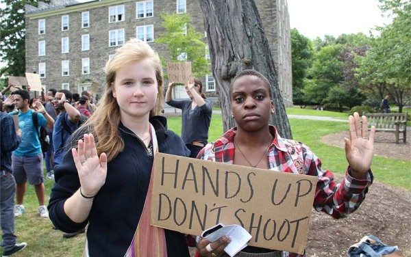 Students raise their hands while displaying a sign that reads hands up, don't shoot