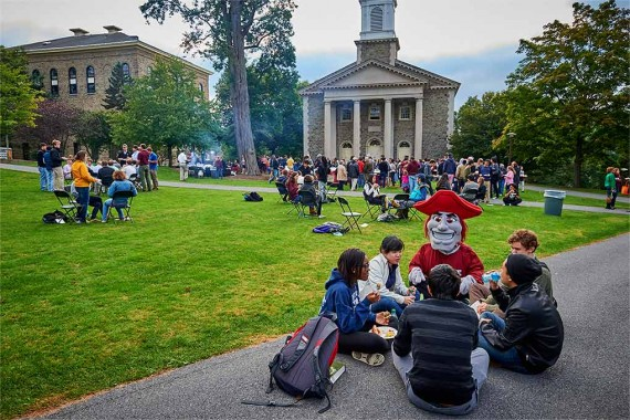 Raider sits with students eating on the Academic Quad