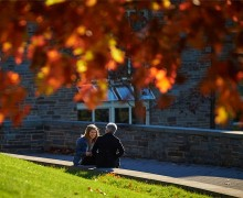 Student speaks with family member framed by autumn leaves