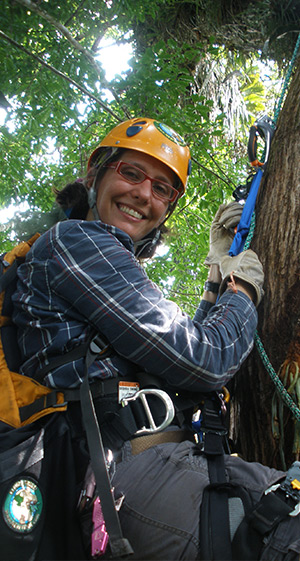 Catherine Cardelús climbing tree in harness and helmet