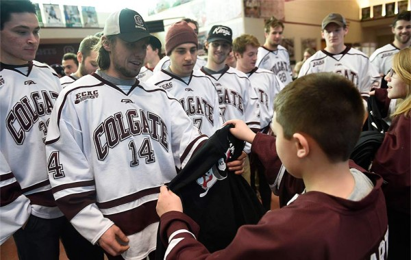 The hockey team in their jerseys meet their honorary coaches from Camp Good Days