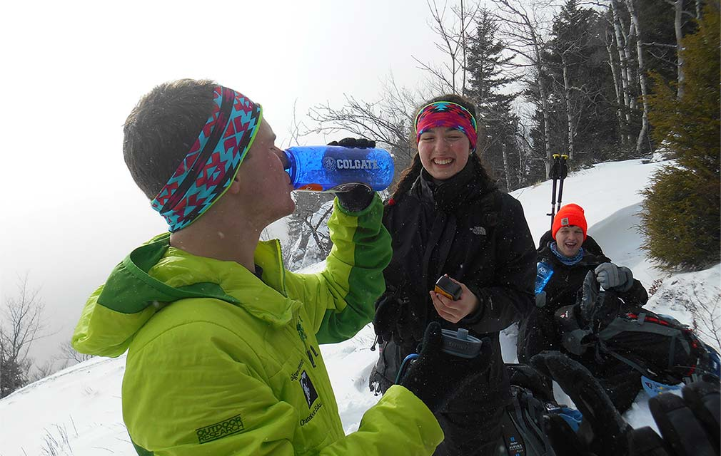 Student in snow gear drinks from a Colgate water bottle among friends