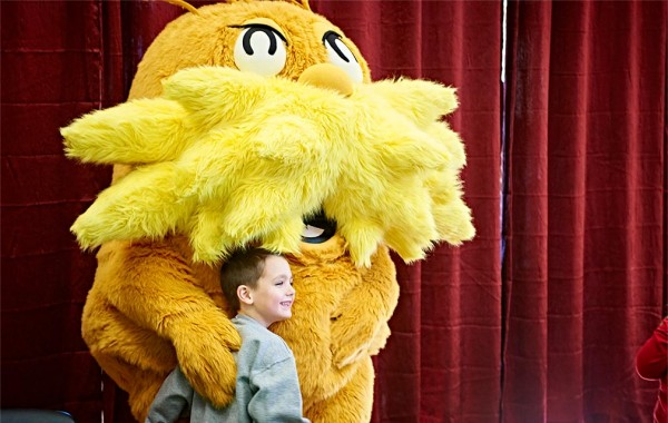 Child poses for a picture with a mascot of Dr. Seuss's Lorax